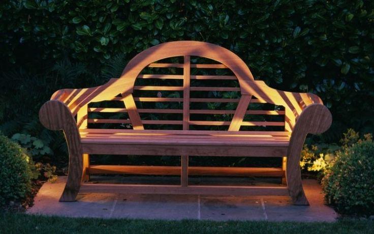 banc de jardin en bois, entouré de buis en boule et lampes solaires