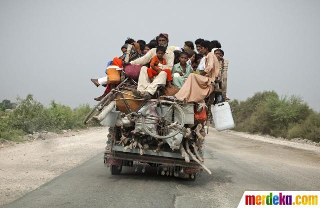 Sejumlah orang menumpang mobil tanpa kap di atas kayu-kayu yang dibawa kendaraan berlebihan penumpang di provinsi Sindh Pakistan.