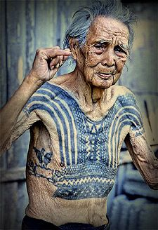 The Last Kalinga tattooist Whang Od stenciling a new tattoo design on Elaine Tima with her kisi in a dark back room at the Batok Festival. E...