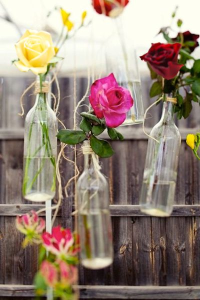 Add Whimsy To Your Event - Hang Roses in Bottles using twine, hang bottles from tree branches or even tent poles.
