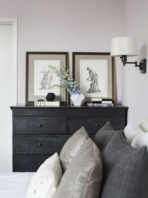 Charcoal gray chest of drawers, light gray wall, various shades of gray pillows. A clean and sharp look.