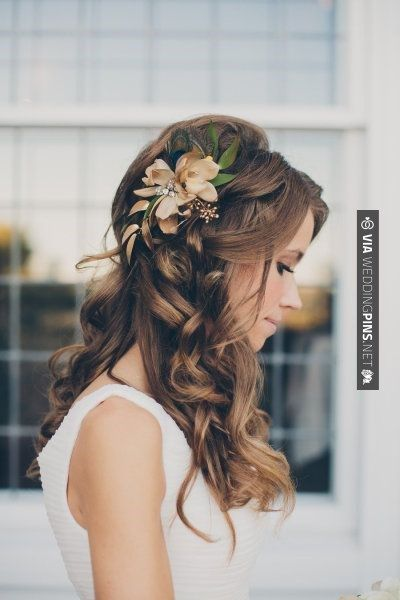 Long brunette hairstyle with soft curls and flower accessorizing the model's hair that is pulled back from her face.