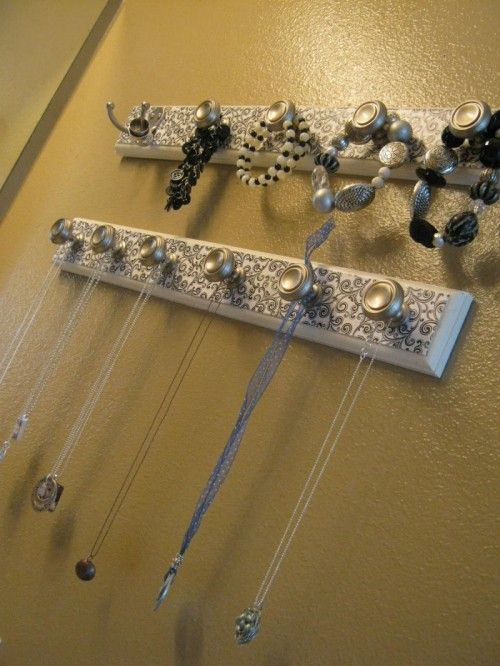 Here is a super easy idea to help you organize your precious jewelry pieces. Make several wall holders of scrap pieces of wood covered with scrapbook paper. Several knobs and hooks on each of them will be perfect to hang your jewelry on them