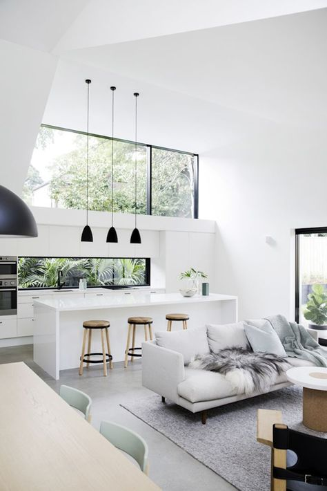 neutral white living room with natural light and pendants over kitchen island in open floor plan concept