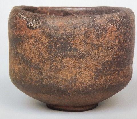 「あやめ」 MOA美術館蔵 黒楽茶碗 銘「あやめ」 作者長次郎 時代桃山時代(16世紀後期) 黒楽茶碗 銘あやめ くろらくちゃわん めい あやめ  千利休の高弟南坊宗啓が著した『南方録』によると、天正15年(1587)五月中に利休は「茶碗 黒 渓蓀」を3回用いているが、本図の茶碗はそれにあたるものと推測されている。外箱蓋表に「あやめ 長次郎作 旦(花押)」、内箱蓋表に「長次郎焼 茶碗」と宗旦が書き付けている。同じく長次郎作の茶碗「まこも」の中箱に、久須美疎安が「あやめハ千宗守ニ有之」と記しているので、「あやめ」は、宗旦から一翁宗守、さらに官休庵に伝わったと思われる。後に永楽善五郎の所持となり、草間伊兵衛に譲られた。「大黒」や「俊寛」の形式とも違った独特の作行きの茶碗で、侘びの趣きの深い名碗の一つである。全体がかなり厚手に成形されており、胴にわずかにくびれがつけられていて、肌の起伏に言い難い趣きがある。高台は小振りで低く、高台内の兜巾は渦がなくおとなしい。畳付には目跡が5つ残っている。黒釉には長次郎焼特有の黄褐色のかせがむらむらと現れていて、いかにも古色蒼然とした趣きである。