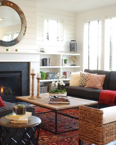 dark sofa, rustic wood and iron table, brown rattan, black ethnic side table, built in white look, carpet, cushions, books and vases