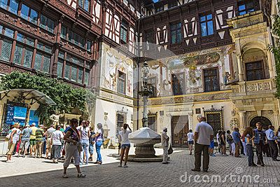 Unidentified tourists wait in line to buy tickets for guided visiting tour of the famous Peles castle and wait in its interior courtyard on July 24, 2013 in Sinaia, Romania.