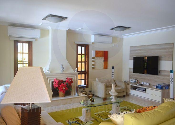 Os ambientes são intimistas e bem integrados. Logo ao cruzar a porta de entrada, um sofá marfim e poltronas revestidas em tecido amarelo acomodam os hóspedes perto da lareira e em frente à telinha.
