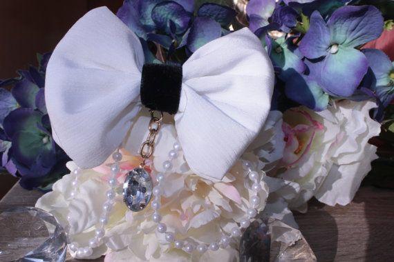 Eine schöne Haarschleife in weiß und schwarz die zu jedem Anlasse passt.  Alle meine Schleifen sind handgefertigt. Sie sind von innen mit Vliesline beschichtet, damit sie eine stabile Form haben und zusätzlich mit Stoffrestn gefüllt, damit sie schön bauschig sind. Sie werden hinten mit einer Krokodilklammer im Haar oder an Kleidungsstücken befestigt.  Maße: 9,5cm x 7,5cm (ohne Band und Perlenanhänger)