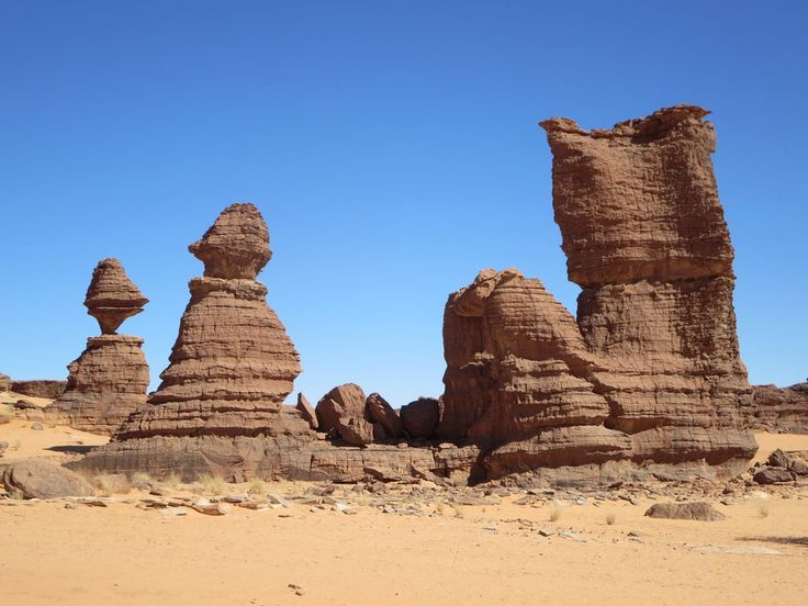 These weathered sandstone pinnacles stand on a hilltop at Abaike in the Ennedi Mountains of northeastern Chad, Central Africa.