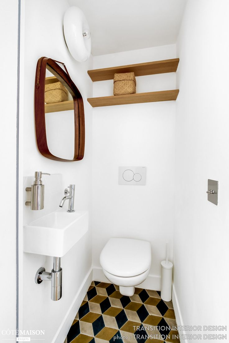 Des toilettes blanches déco vintage tendance avec sol en carreaux de ciment et touches de bois.