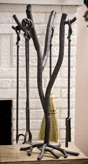 Forged Iron Fireplace Tool Set Forged Iron Accessories - Hand forged iron, 4 piece fireplace set in branch design, includes natural broom. Artfully crafted in a beautiful black finish. The iron is blacksmith built and every hammer blow brings a specific signature of the craftsman.
