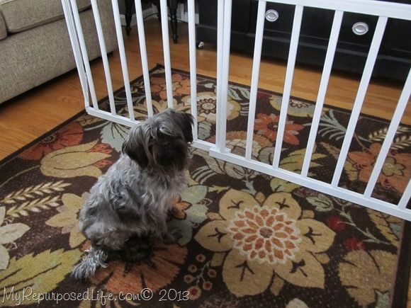 How to make a diy doggie gate using old crib rails.This gate is so versatile, it can be used across irregular doors to keep your dog where you want it.