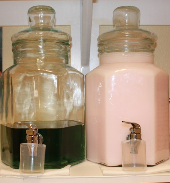 Laundry soap and fabric softener stored attractively in clear glass lemonade carafes.