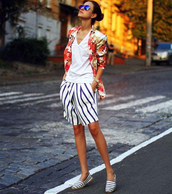 Street style de saia listrada com casaco floral.