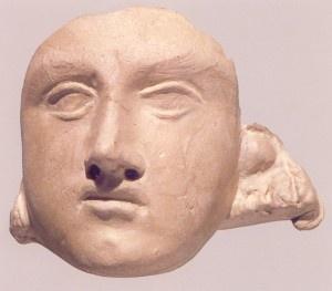 """Máscara femenina- """"Máscara de arcilla, parcialmente dañada, encontrada en una urna. Presenta un rostro correcto y bellamente modelado con los ojos, en forma almendrada, abiertos. Dentro del dibujo de los párpados, ligeramente acentuados, no se ven las pupilas. """""""