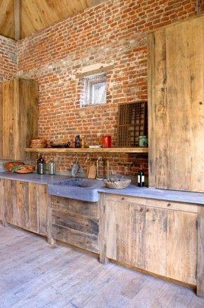 gestort betonnen keukenblad met houten kastjes met kleine staldeuren (hout met ijzerbeslag) en wasbak met grote kraan