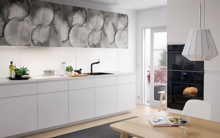 A medium size kitchen with doors in grey abstract patterns combined with white doors and drawers. Shown together with black sink, mixer tap and dark grey oven.