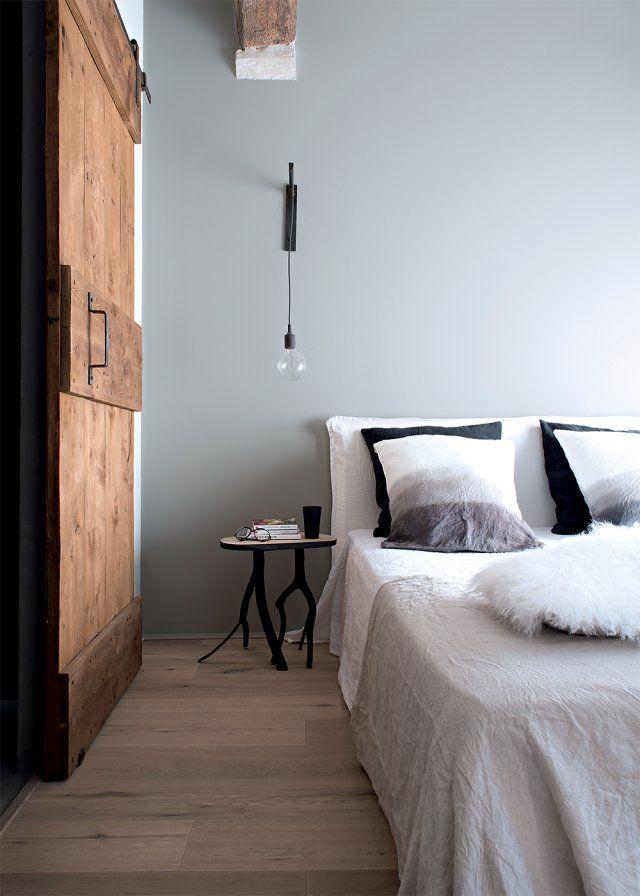 À l'étage, la chambre parentale est baignée de lumière. La porte coulissante qui mène à la salle de bains a été réalisée -avec du bois de récupération par la maison Laurent Passe. Table de chevet, Les Affaires étrangères à Uzès. Applique sur mesure par ml-hdesign et ampoule Muuto. Lit et draps en lin AM-PM, taies d'oreillers en lin, 3 Suisses.