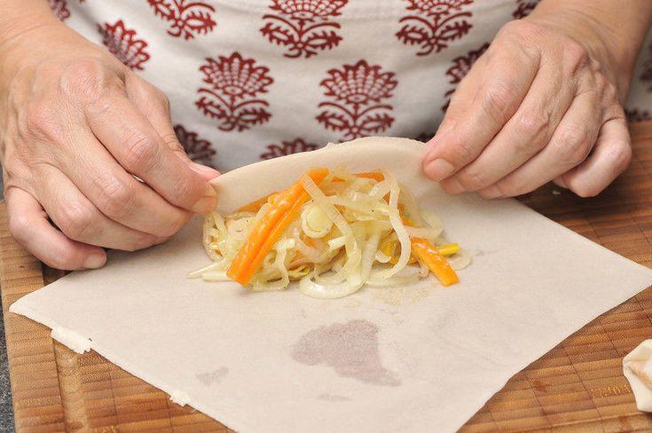Colocar una hoja de masa para rollo primavera con una esquina apuntando hacia nosotros. Colocar un poco de la mezcla de verduras salteadas en forma de rectángulo. Cubrir con el triángulo de masa que queda como pico.