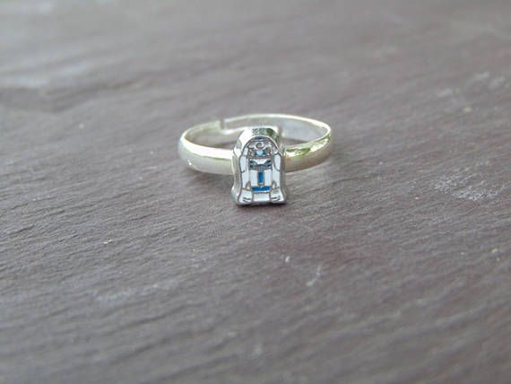 A fantastic little Star wars R2D2 Ring R2D2 is approx 8x5mm and sits on a silver plated adjustable ring base The ring is adjustable, the smallest size is around 5.5 cm in diameter and it stretches comfortably to around 6.5 cm. This ring is very subtle, and would be perfect for any occasion A perfect gift for a friend or relative, or a lovely treat for yourself I very much enjoy putting together my pieces myself, if you have any questions regarding my items, please dont hesitate to send me…