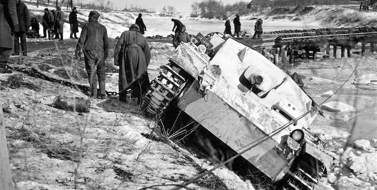Germans prepare to rescue a StuG III Ausf and who fell from a train rail within a river. The vehicle uses winter camouflage.