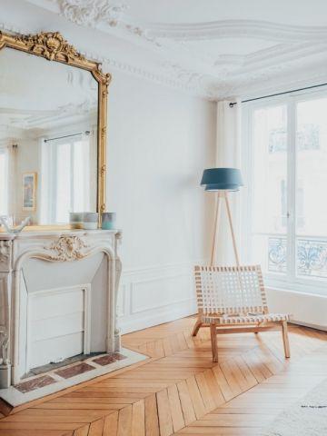 """miroir ancien doré au dessus de la cheminée de marbre blanc, murs et plafonds moulurés blancs, parquet en chêne """"point de hongrie"""" poncé et vitrifié pour un résultat clair et lumineux"""