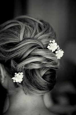 Twisted updo dressed up with some little white flowers. A super cute updo idea for a bride who is having a rustic wedding!