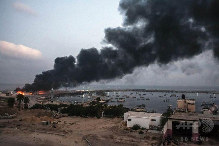 イスラエル軍の攻撃を受け燃えるパレスチナ自治区ガザ地区(Gaza Strip)の港の建物(2014年7月29日撮影)。(c)AFP/LOULOU D'AKI ▼29Jul2014AFP|ガザ唯一の発電施設が稼働停止、イスラエル軍攻撃受け http://www.afpbb.com/articles/-/3021772