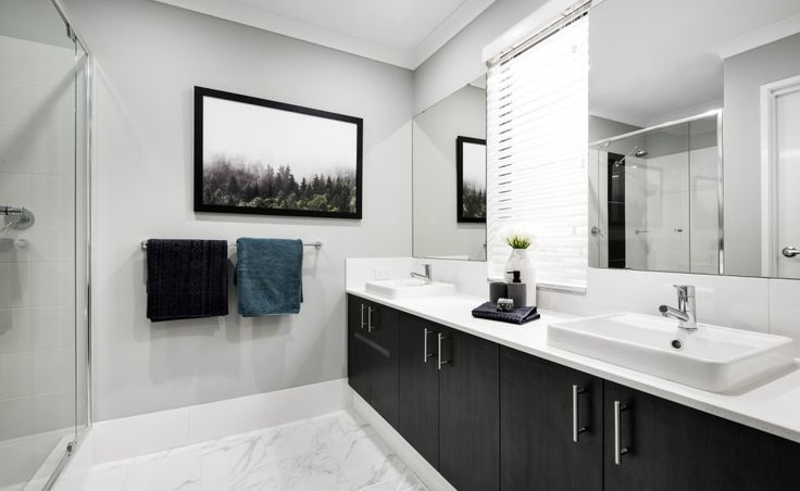 The ensuite features semi-inset vanity basins, mixer taps and glass semi-frameless pivot screen door