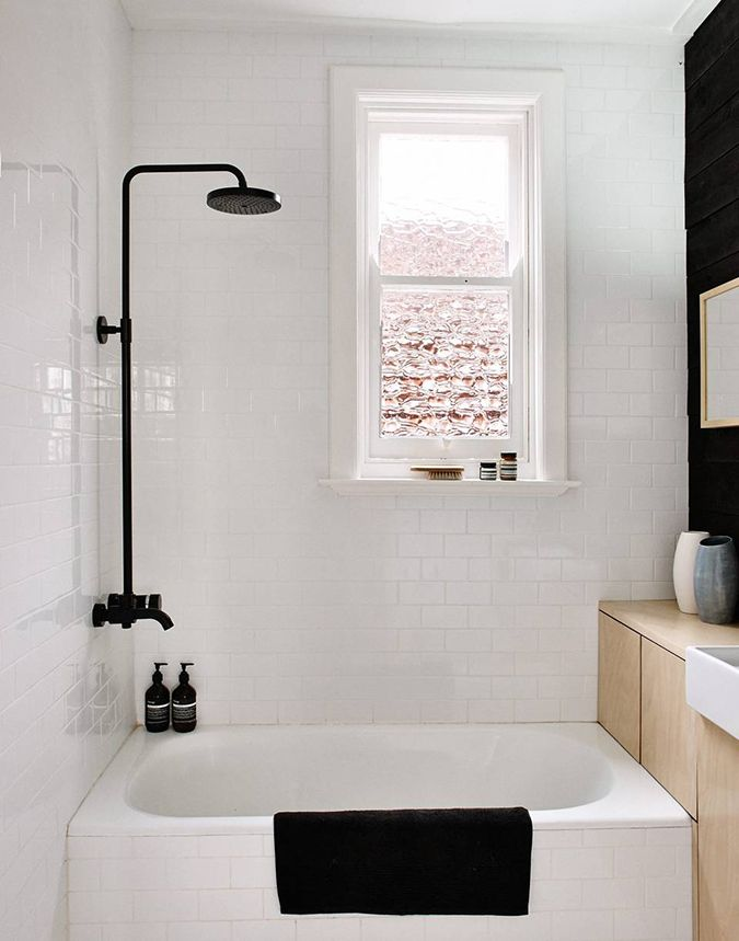 Lite bad med badekar, spesialtilpassede skap og svartlakkert armatur.