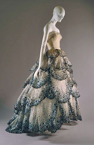 Christian Dior dress, 1950. The blue, black, and silver rhinestones against the beige dress is exquisite; the pattern of petals gradually increasing in size to the bottom; the detailed sequins throughout the gown as well as on the bodice: brilliant.