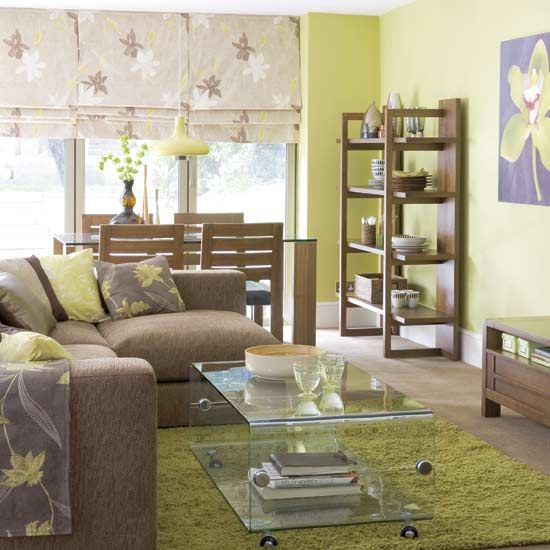 Even understated green will add life to a room.  The green with the earth tone sofa and carpet, and wooden furniture really bring the room together.  www.whitefence.com