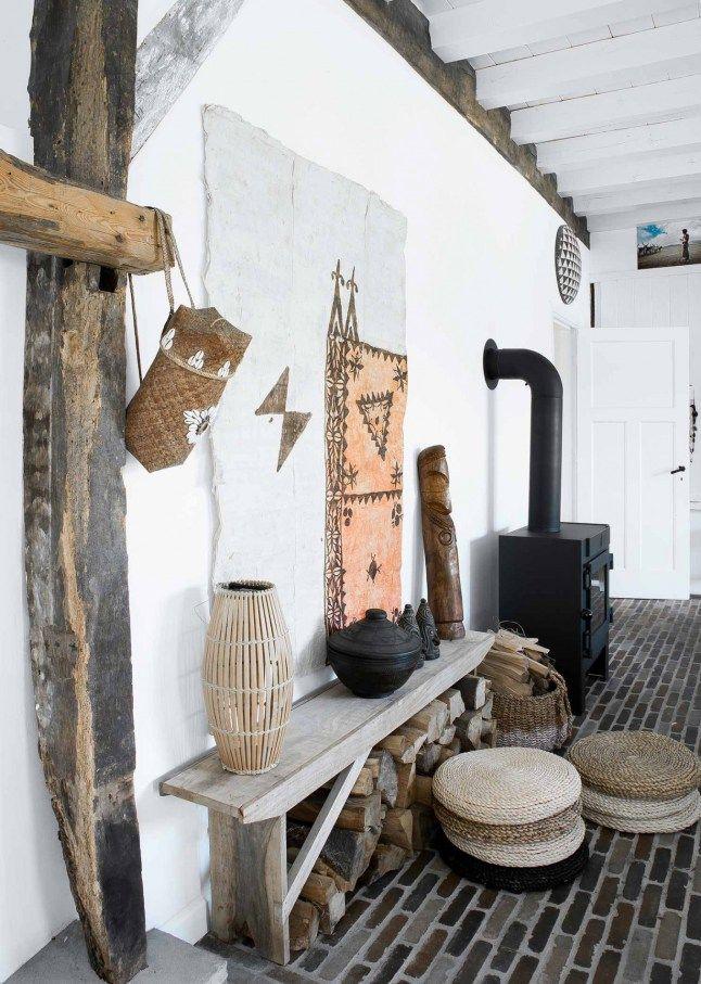 Une ambiance bohème avec un banc en bois, un poêle noir, coussin de sol en osier