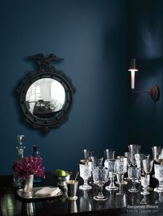Table with a variety of glasses against a deep blue wall.gentlemans grey