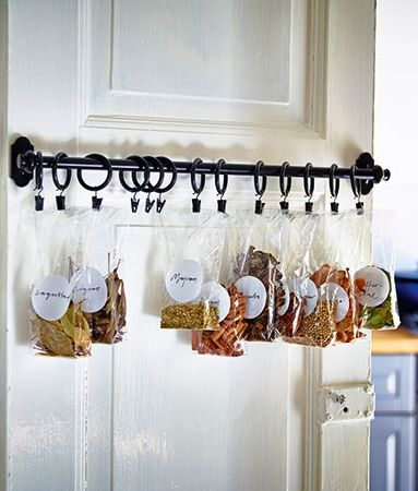 Free up shelf and countertop space by hanging your spice bags with this multitasking rod. Either invest in a 5-pack of matching S-hooks (about $3, IKEA), or shower curtain rings with mini clamps to grab onto spice bags. You can also double the length by connecting two rails using one bracket. FINTORP rail, about $9; IKEA