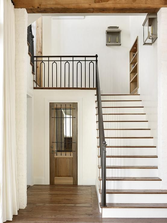 Long ivory curtains hang over hardwood floors in a rustic cottage foyer boasting wood and glass wine cellar door accented with wrought iron bars located under a white staircase fitted with wooden treads and an iron hand rail and spindles.