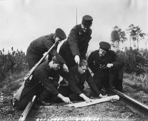 1914 - Soldats étudiant la position des Allemands avec une carte posée sur la voie ferrée : photographie de presse / Agence Rol