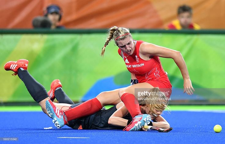 TOPSHOT - Britain's Lily Owsley (R) falls over Netherlands' Caia van Maasakker during the women's Gold medal hockey Netherlands vs Britain match of the Rio 2016 Olympics Games at the Olympic Hockey Centre in Rio de Janeiro on August 19, 2016. / AFP / MANAN