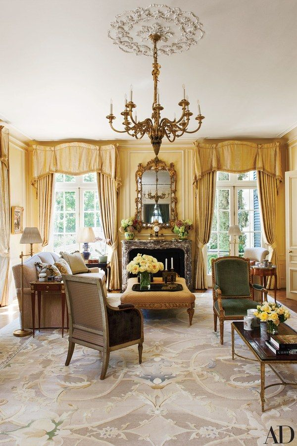A Louis XVI chandelier crowns the living room at a 1920s San Francisco–area home by Arthur Brown Jr. that was renovated by Douglas Durkin Design. The space is appointed with a Durkin-designed ottoman by C. Mariani Antiques and a custom-made rug by Beauvais Carpets; a Brunschwig & Fils fabric curtains the windows.