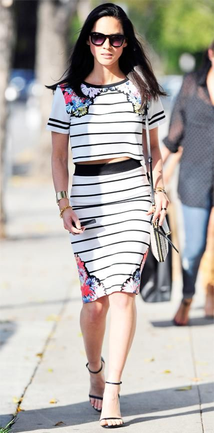 Out and about in Beverly Hills, Olivia Munn bared a sliver of midriff in a striped-and-floral print MinkPink crop top and matching pencil skirt with a printed cross body purse, a stack of gold bracelets, and black ankle-strap Stuart Weitzman sandals. InStyle.com