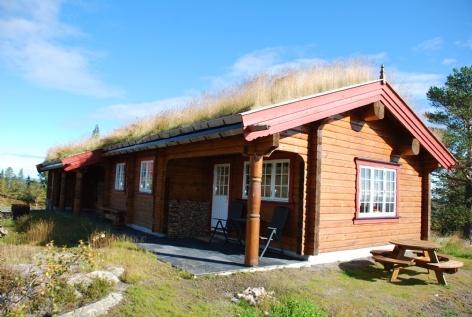 HYTTE BJØRNEBU 4.  Med hytte og bod under samme tak betrakter vi denne modellen som den mest praktiske i Bjørnebuserien. En koselig hytte som med sin spesielle takløsning kryper godt inn i terrenget.