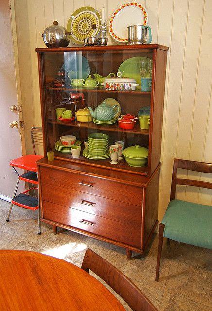 木製のキャビネットを食器棚として利用したアイデア。中に並ぶ食器もレトロな雰囲気のものであわせられている。