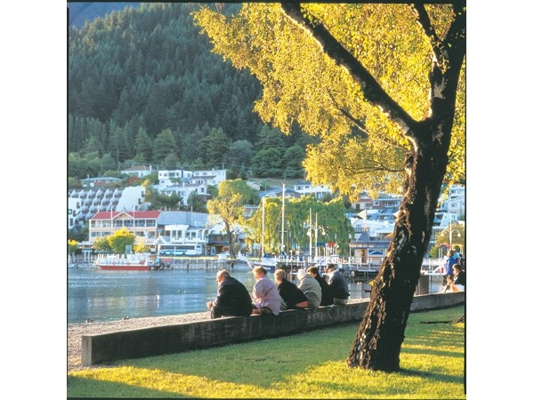 A group of friends relax on the waterfront of Lake Wakatipu in Queenstown.