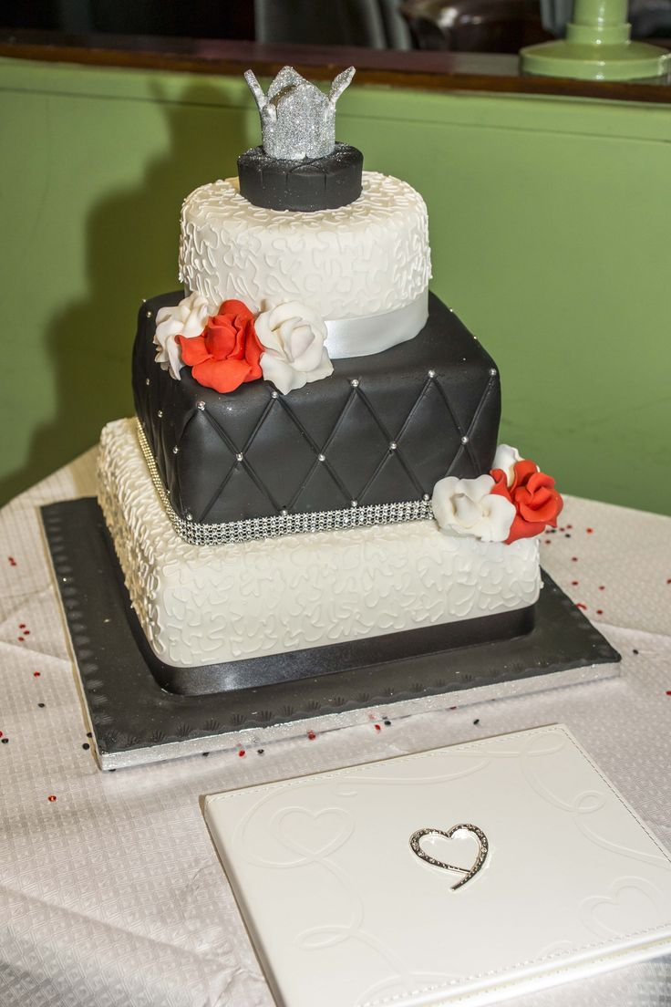Three tire black and white cake with red roses.
