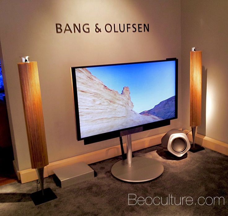 """Bang & Olufsen home theater with the Beovision Avant 55"""" on the motorized floor stand. The speakers are the Beolab 18 with oak grills and the Beolab 19 subwoofer in grey."""