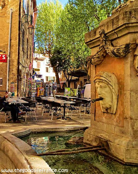 """Cotignac, Provence. Plane trees cast shade over the bubbling fountain """"Les Quatres Saisons"""" and the tables that spill onto the pavement from the restaurants and cafés, like the ever popular café du Cours, and the benches where locals sit and watch the world go by."""