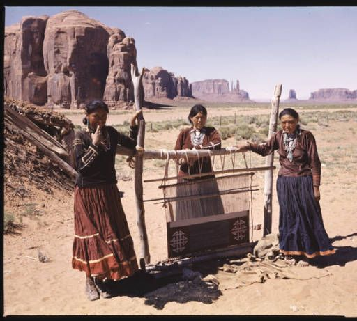 Loom in the Desert. With mighty rock formations in Monument Valley, Arizona as a background, three Navajo Indian women stand near their loom. They are famous for their rugs, a native craft which still persists as a means of life on their Reservation. (Photographer's caption) :: Colorado Plateau Digital Archives Selections