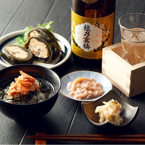 いかの赤作りは日本近海で漁獲される「するめいか」を細切りにし、いかわた(肝臓)と和え、調味・熟成させております。山海漬は大根、きゅうりを細かく刻み数の子を和え、酒粕に漬け込み辛味をきかせているのが特徴です。だし茶漬は手塩にかけて漬け込み、丁寧に焼き上げてほぐしたアラスカ産の紅鮭を使ったお酒のシメにぴったりのお茶漬です。鮭の昆布巻はキングサーモンの中骨を昆布で巻き、醤油・みりん・清酒・だし汁などで、じっくりと煮込みました。越乃寒梅はほのかな吟醸香があり、口当たりは軽く滑らか、飲み口が良く、後味に旨味が拡がる、ふくらみのある上品な味に仕上がっています。