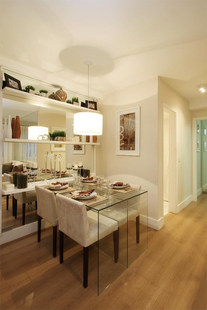 A parede da sala de jantar foi revestida com espelho lapidado e polido, com prateleiras em fórmica branca para comportar os adornos e também funcionar como aparador para a mesa de jantar. Essa, em vidro com cadeiras em suede cru e pés em madeira http://ow.ly/c9dnq